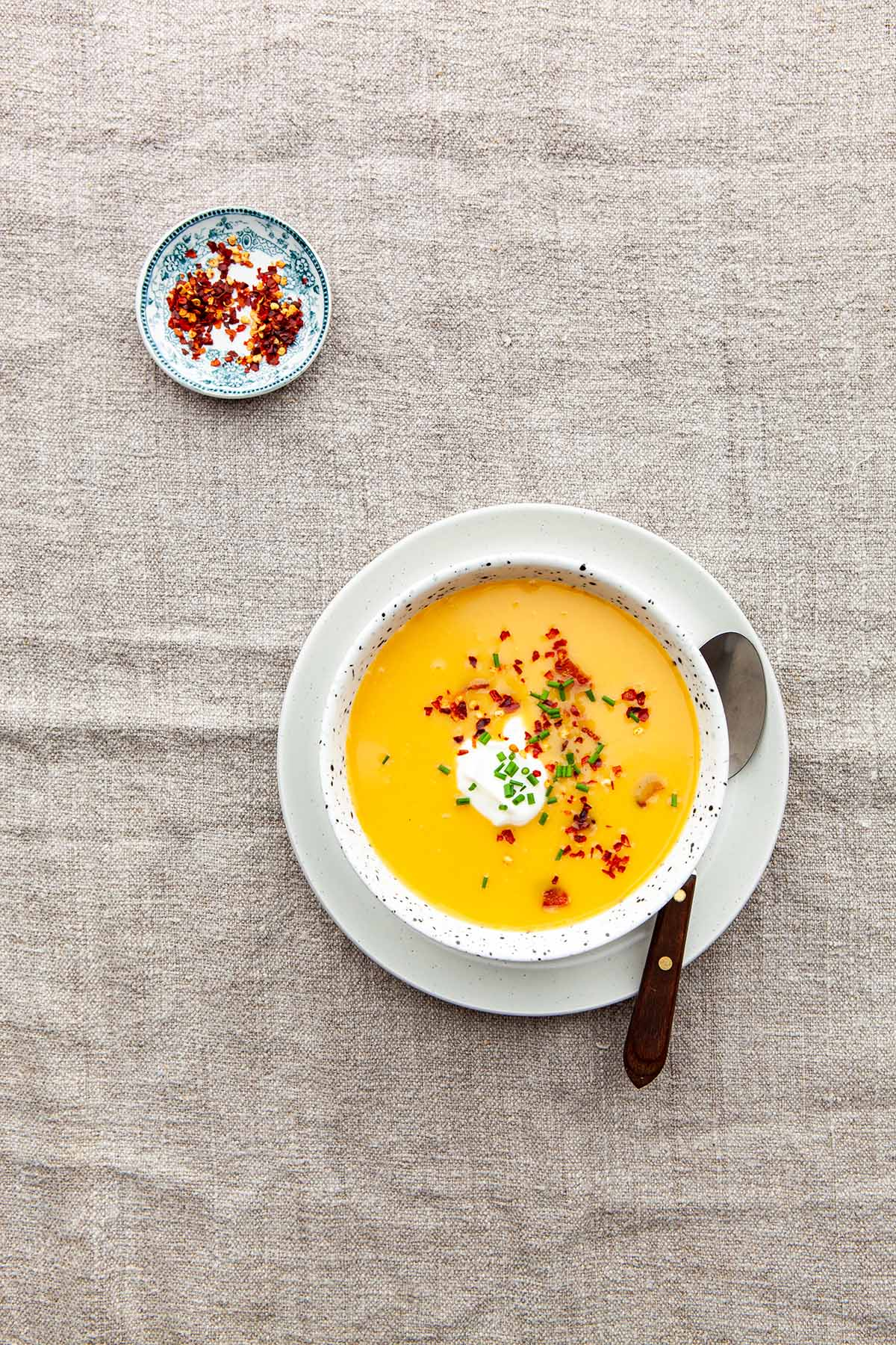 A bowl of spiced butternut squash and sweet potato soup on a linen tablecloth near a small pinch dish of chilli flakes mixed with flaky sea salt.