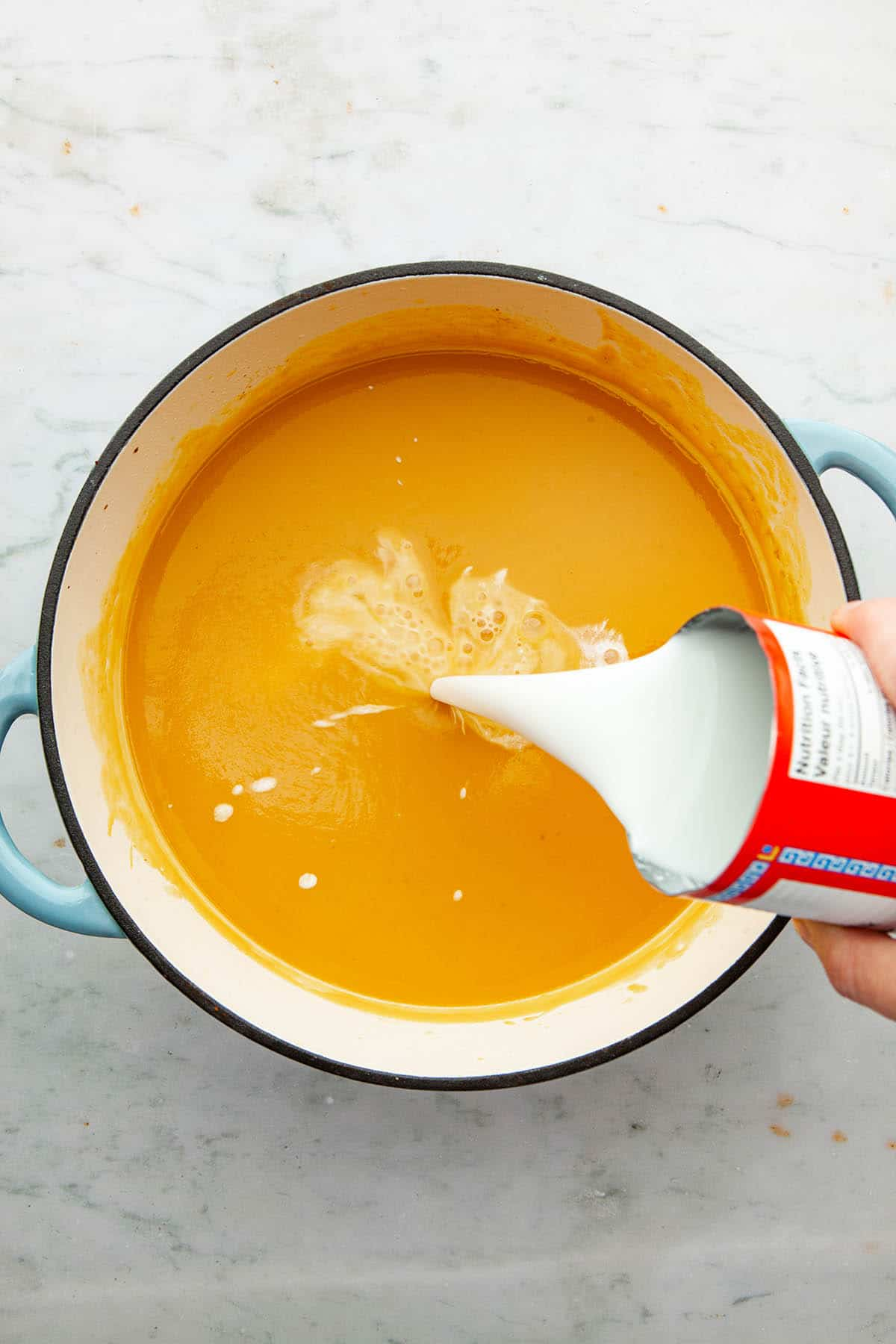 A hand pouring a can of coconut milk into a pot of puréed soup.