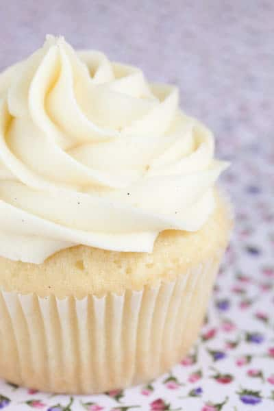 A single vanilla cupcake with vanilla frosting on flowered fabric.