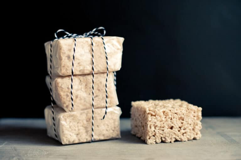One chai-spiced rice krispie square on a board next to three wax paper-wrapped squares tied with twine.