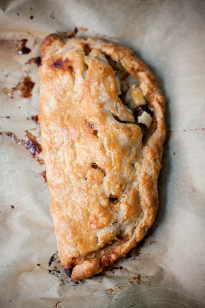A fully baked Cornish pasty on a parchment lined baking sheet.