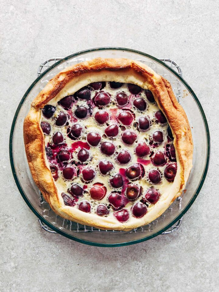 A baked cherry clafoutis in a clear baking dish cooling on a rack.