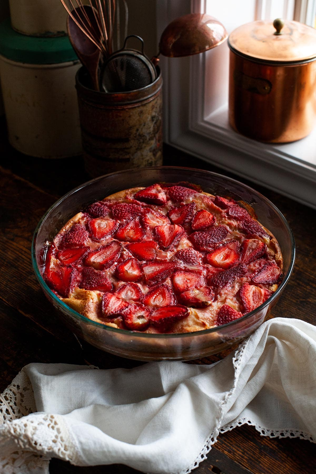 A whole strawberry clafoutis cooling on a table near a window.