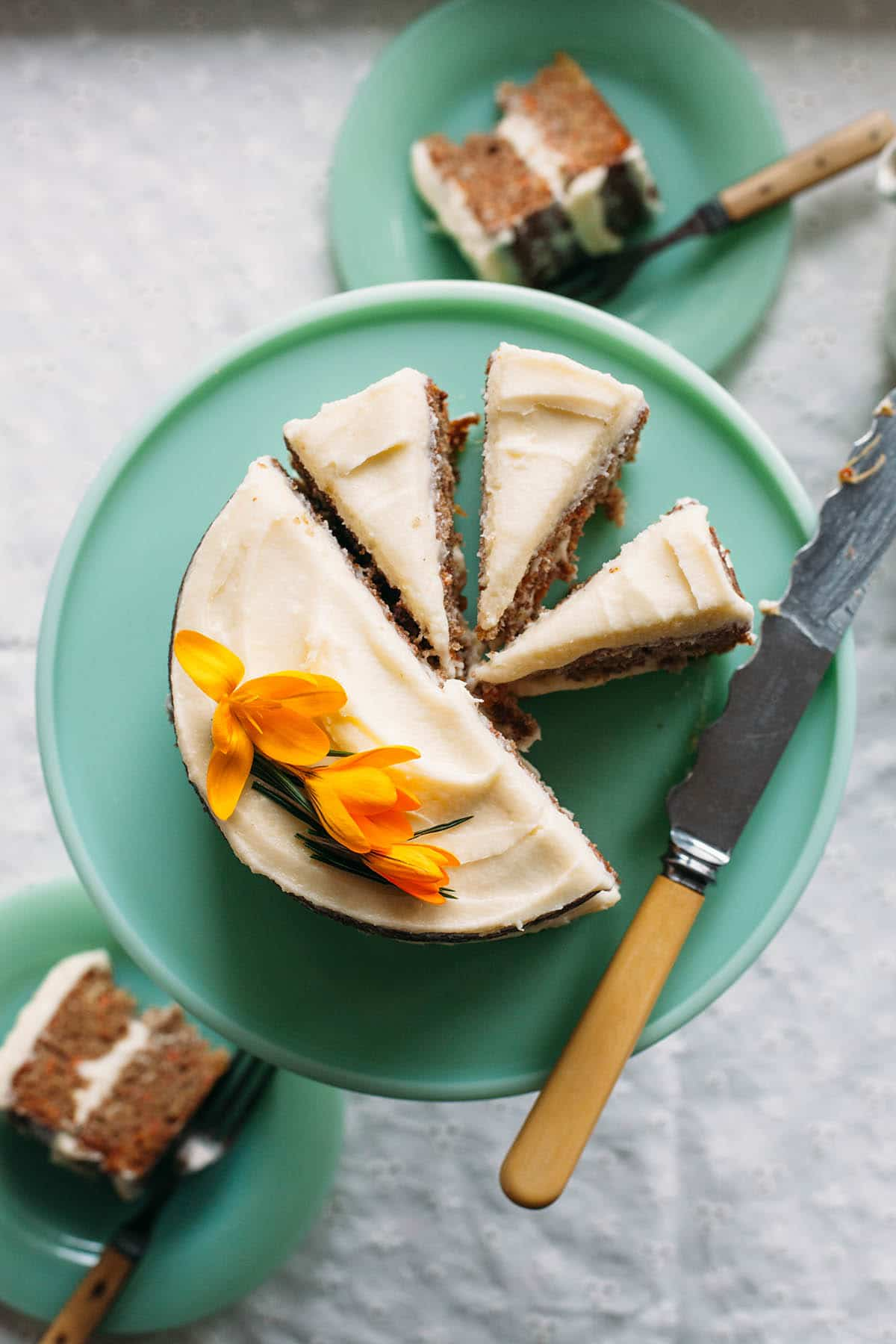 Sliced spiced carrot cake with pineapple on a cake stand.