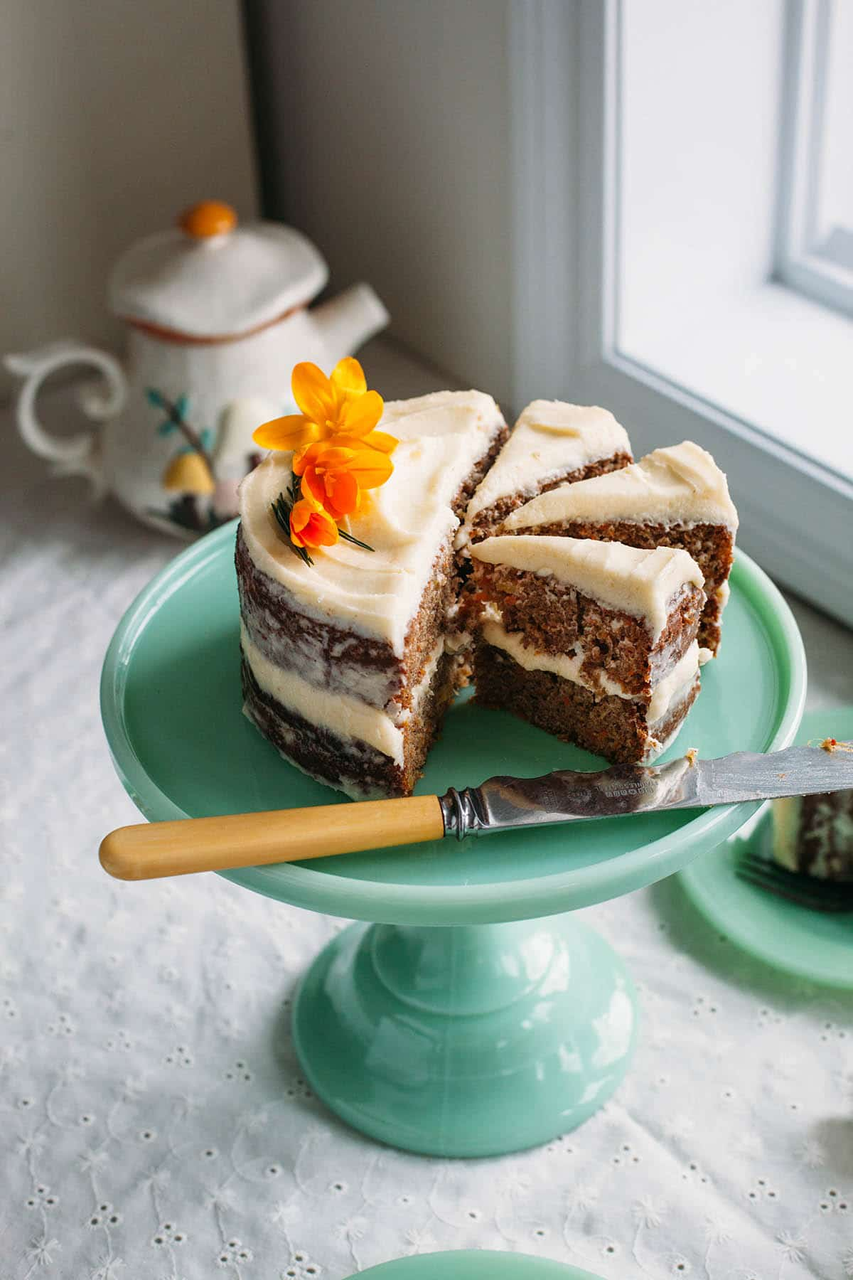 A spiced carrot cake with pineapple cut into slices on a green cake stand.