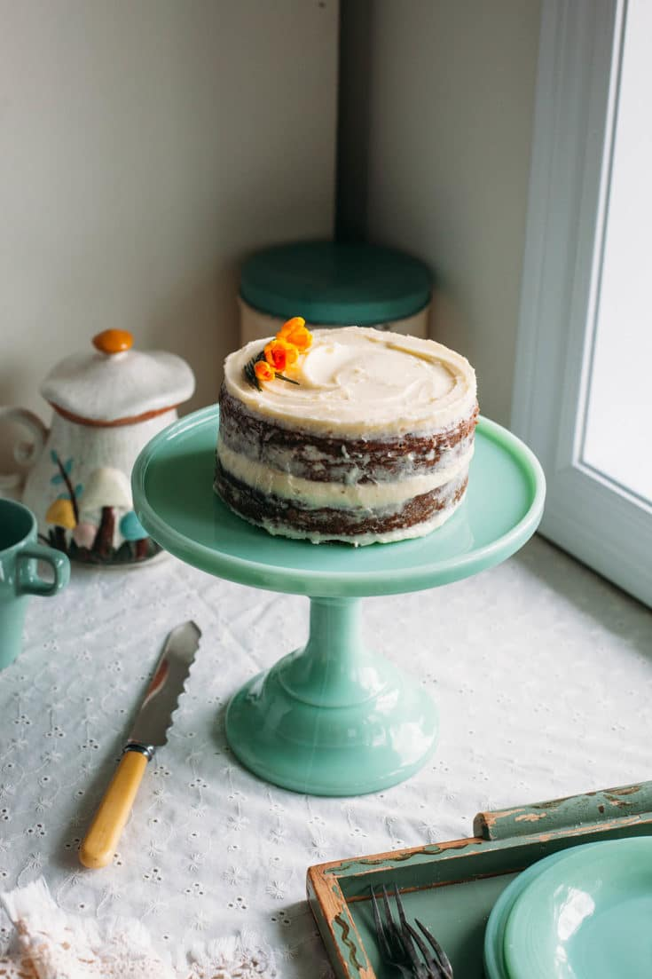 Spiced carrot cake with pineapple on a green milk glass stand.