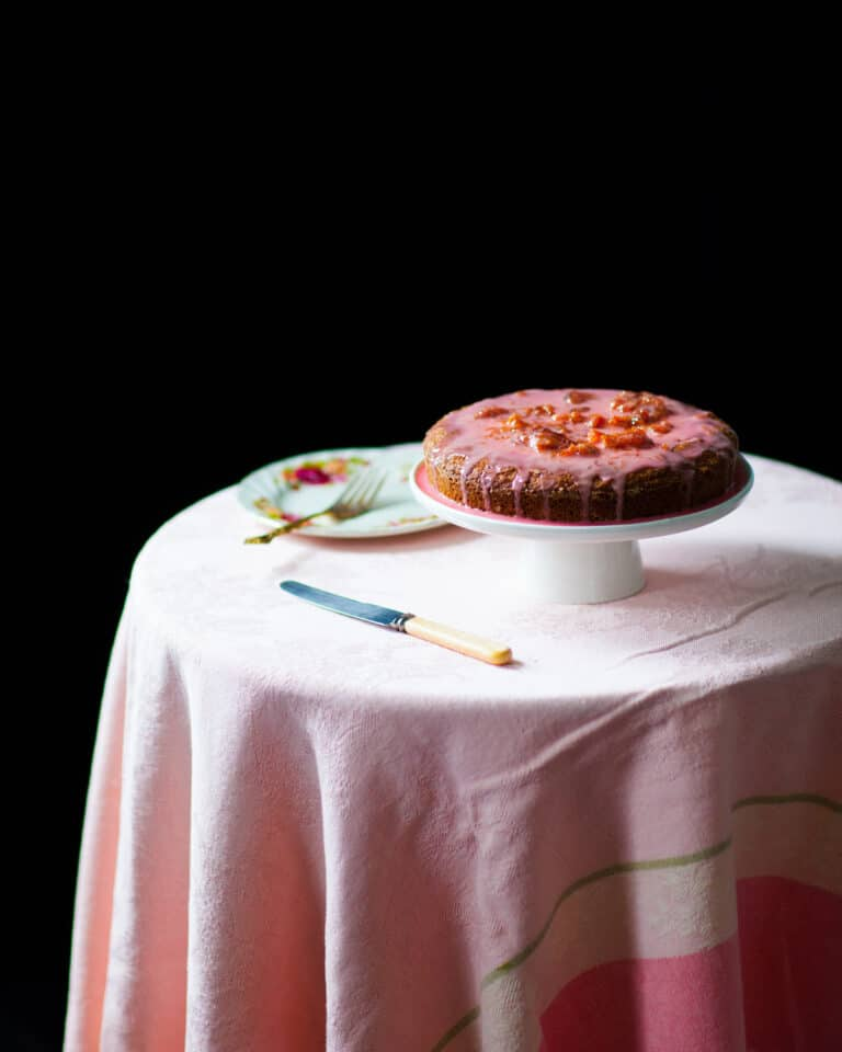 A Coconut Blood Orange Cake With Blood Orange Glaze on a cake stand on a small round table.