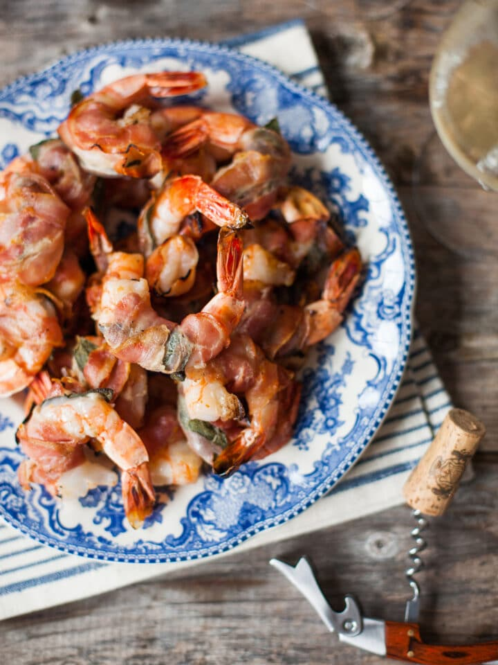 A plate of grilled shrimp with fresh sage and pancetta on a blue and white plate.