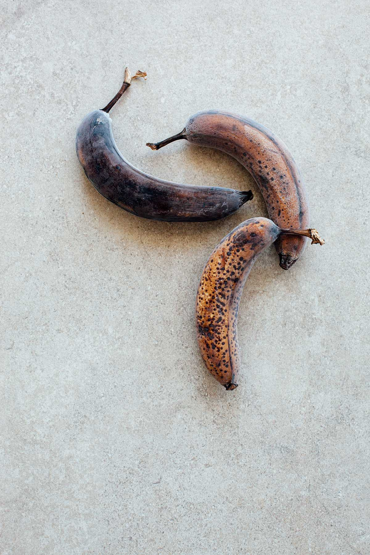 Frozen overripe bananas on a stone background.