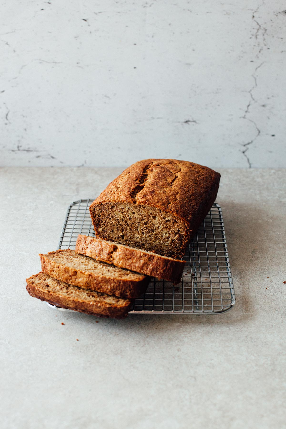 A sliced buckwheat banana bread on a cooling rack.