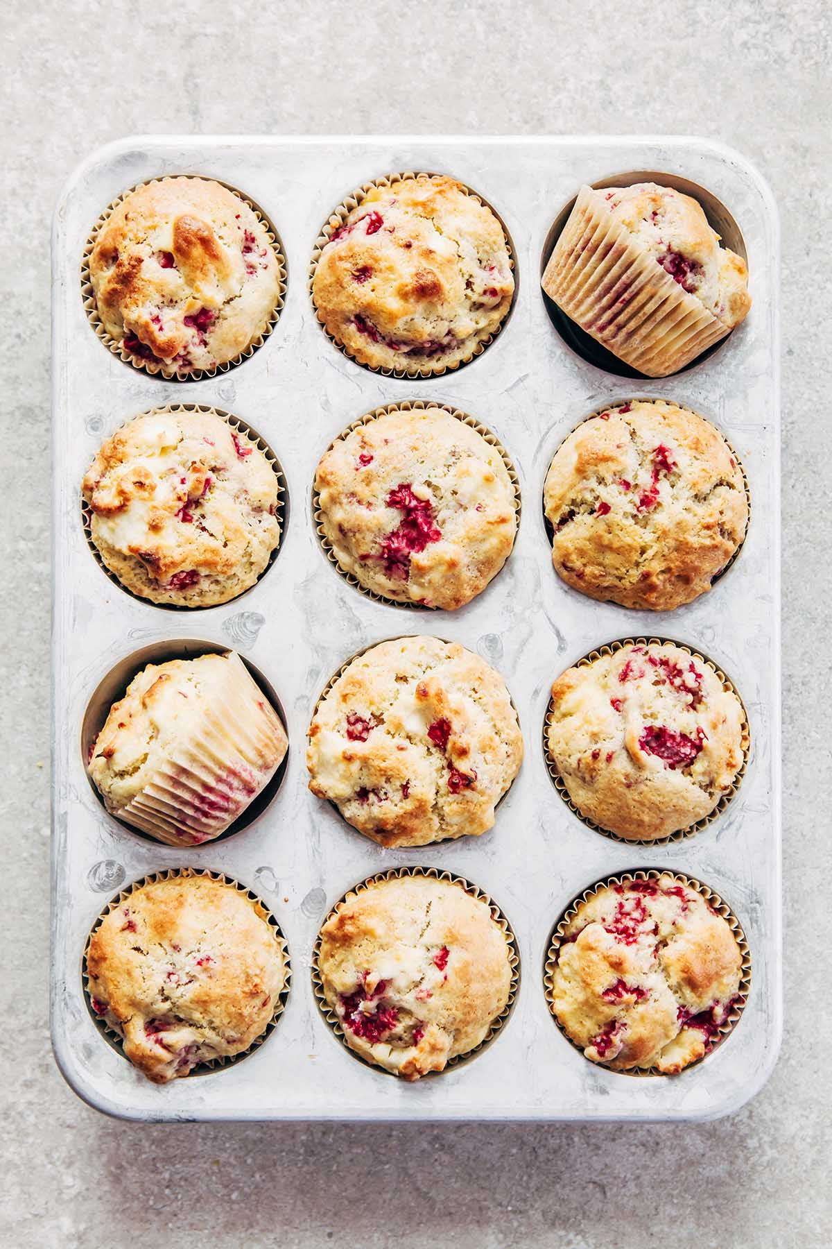 A tin of 12 baked raspberry lemon cream cheese muffins.