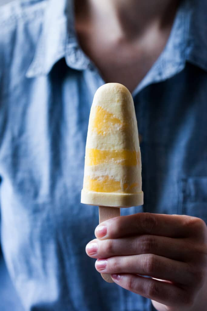 A woman's hand holding a popsicle from a batch of lemon curdsicles.