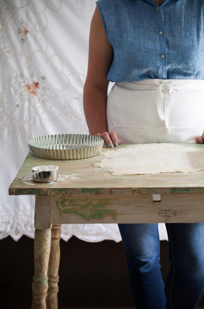 A woman wearing a blue shirt and a white apron with rolled out quiche dough.
