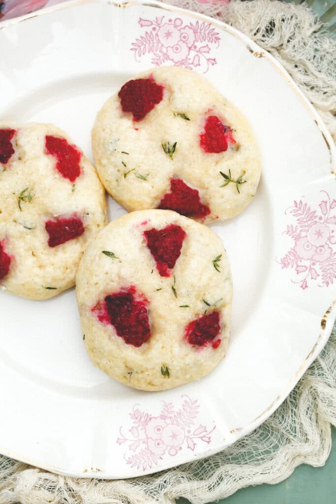Close up of three raspberry thyme scones on a plate.