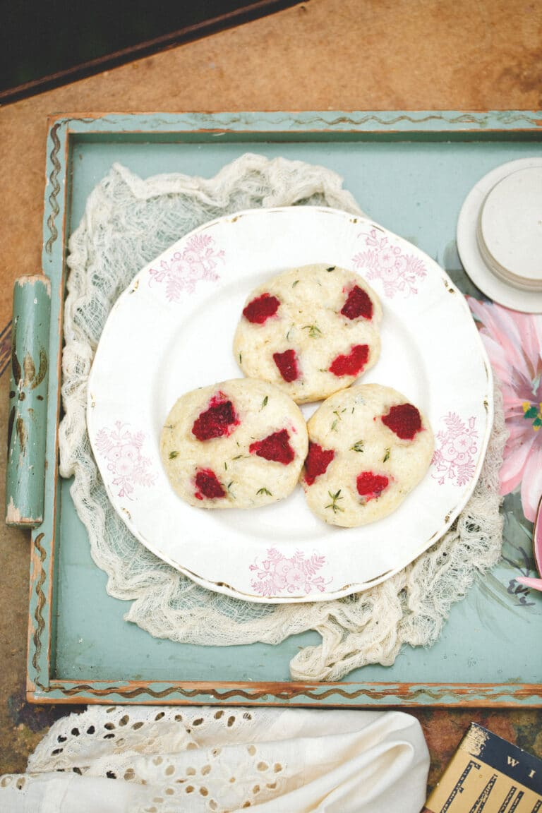 Raspberry thyme scones on a pink and white plate on a green floral serving tray.