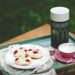 Scones, a thermos, and a tea cup on a table in the grass.