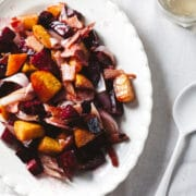 An oval platter of Bacon Fat-Roasted Beets With Double Smoked Bacon And Shallots.