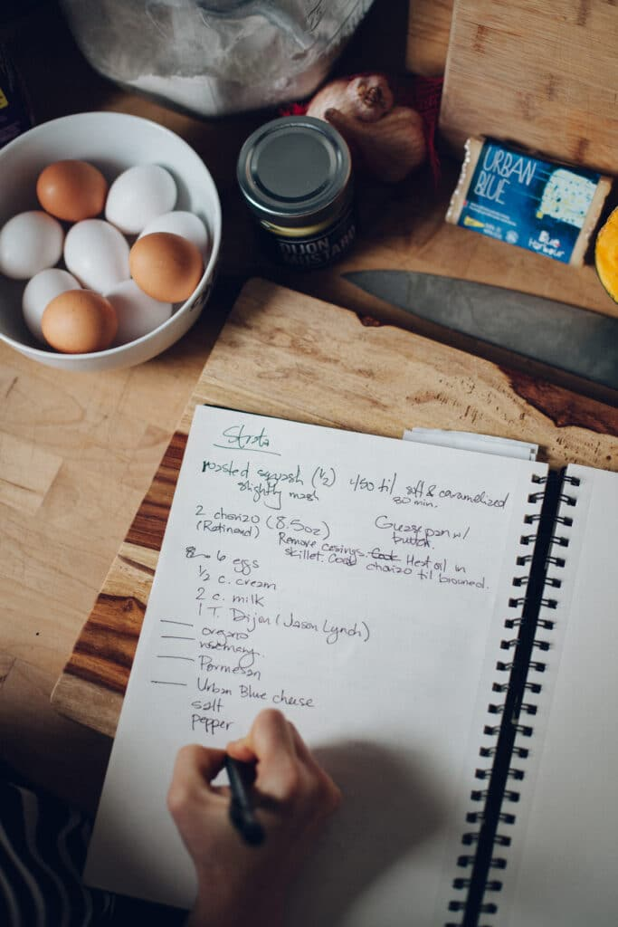 A hand writing a recipe into a large notebook.