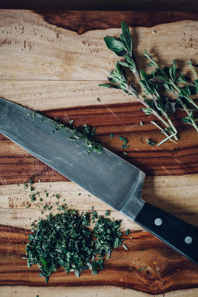 Chopped herbs ona cutting board with a chef's knife lying in the middle.