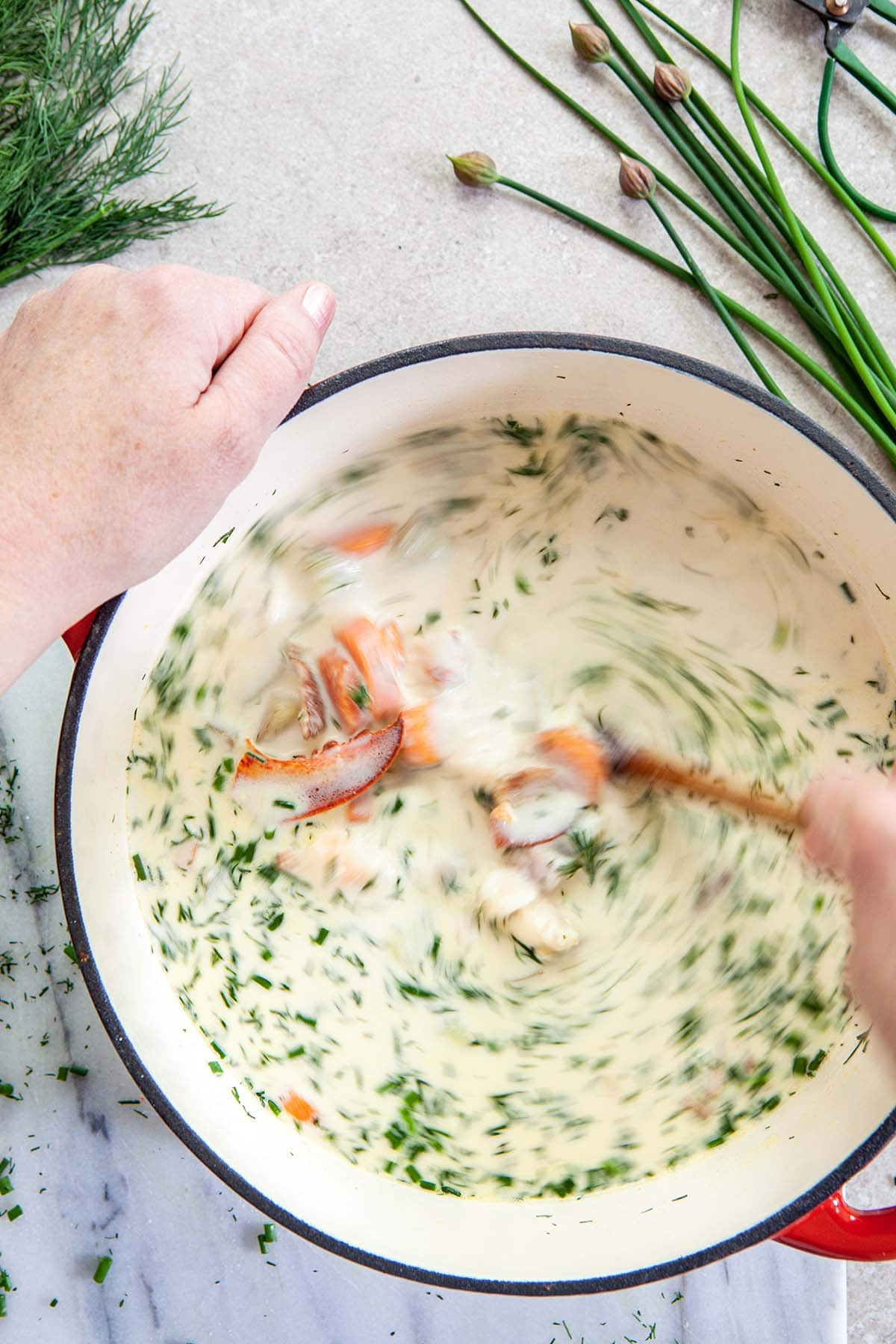 A hand stirring a pot of soup on a amrble surface with chopped dill and chives nearby.