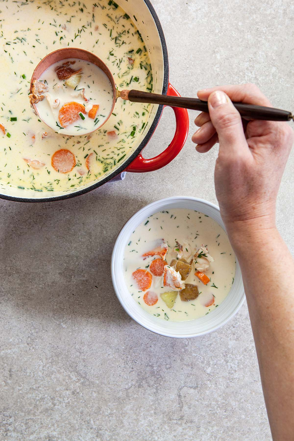 A woman's hand holding a ladle full of chowder from a large orange pot with a bowl of chowder on the table below.