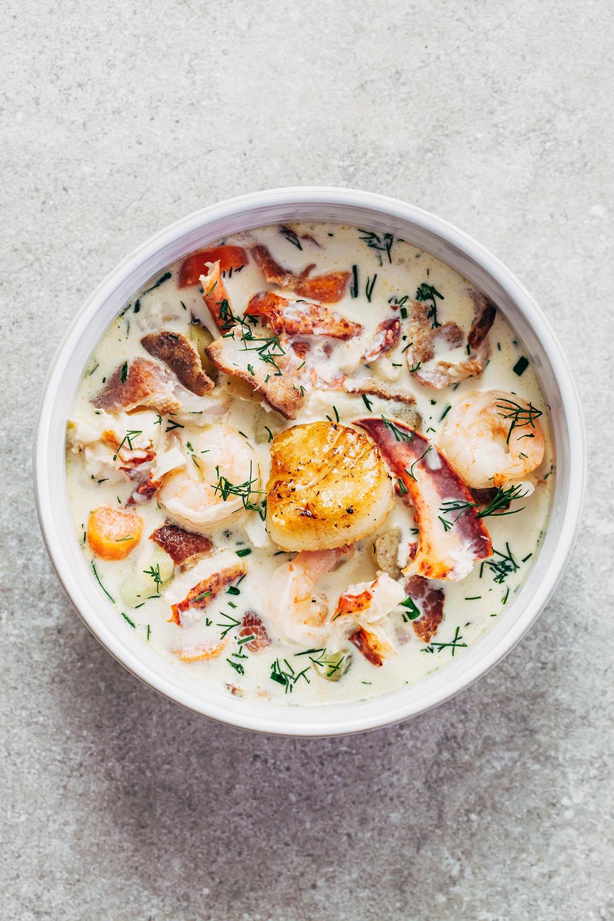 Overhead shot of a bowl of nova Scotia seafood chowder loaded with lobster, haddock, shrimp, potatoes, and bacon, with one golden pan-seared scallop on top.