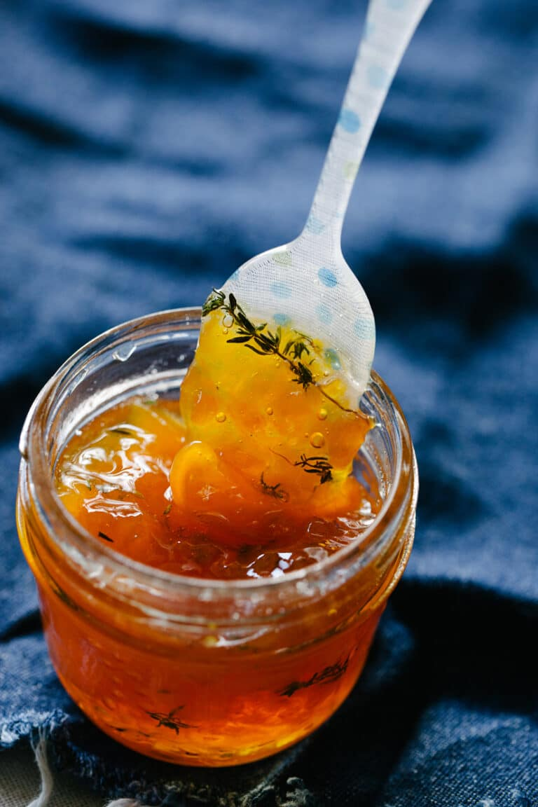 A small jar of maple peach whisky jam with a polka dot spoon.