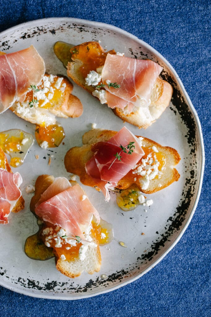 Slices of toasted baguette on a round pan topped with prosciutto, blue cheese, and maple peach whisky jam.