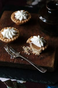 Three mini Cape Breton butterscotch pies topped with whipped cream on a wooden cutting board.