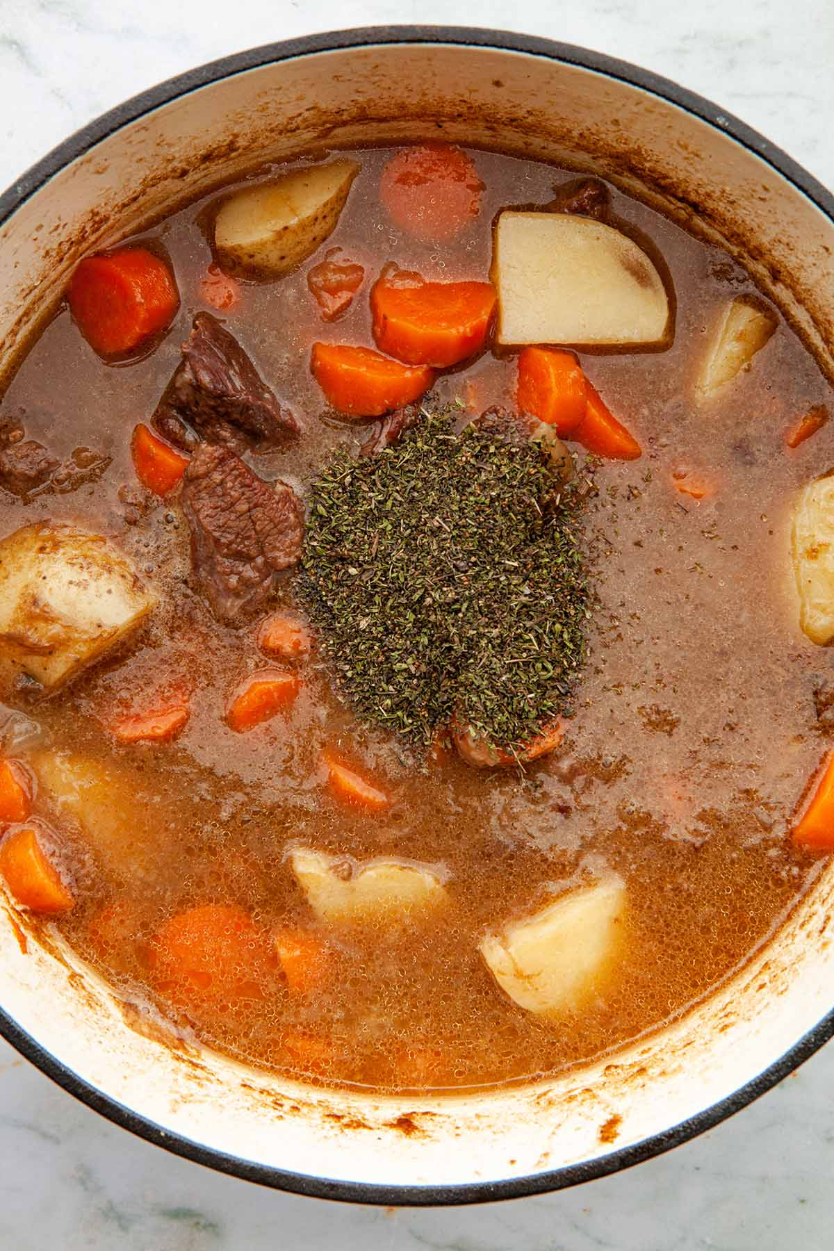 A pot of cooked beef, broth, onions, carrots, and potatoes with a small pile of dried summer savory sitting on top of the mixture.