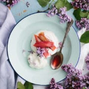 Cider-poached rhubarb pavlova in a bowl on a table surrounded by purple lilacs.