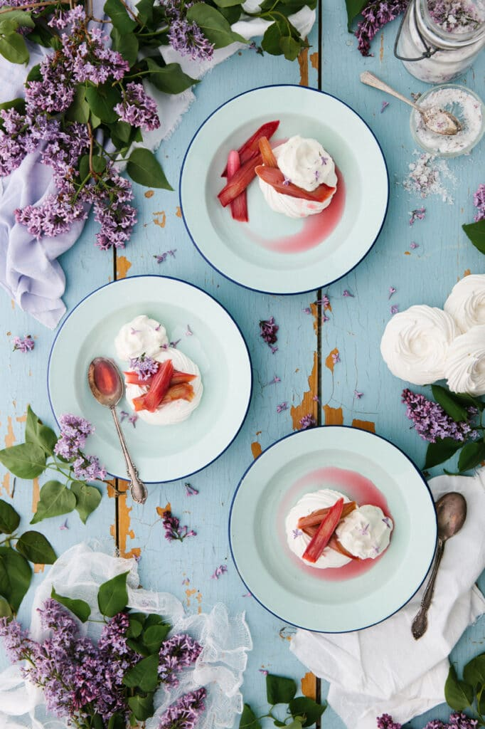 Three individual servings of cider-poached rhubarb pavlova on a blue chippy wood background with lilacs.