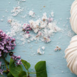 Sugar and lilac blossoms sprinkled on a table next to mini meringue shells.