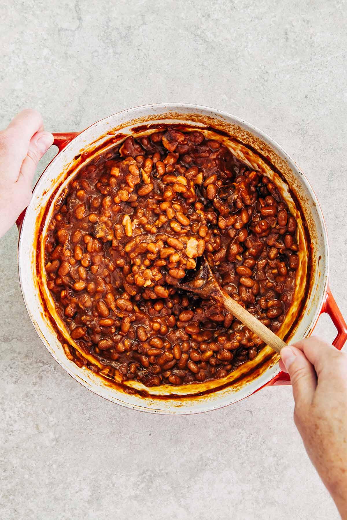 Hands stirring a pot of beans.
