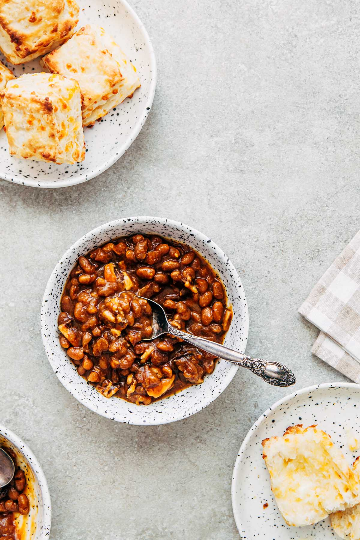 Bowls of homemade molasses baked beans and plates of cheese tea biscuits on the side.