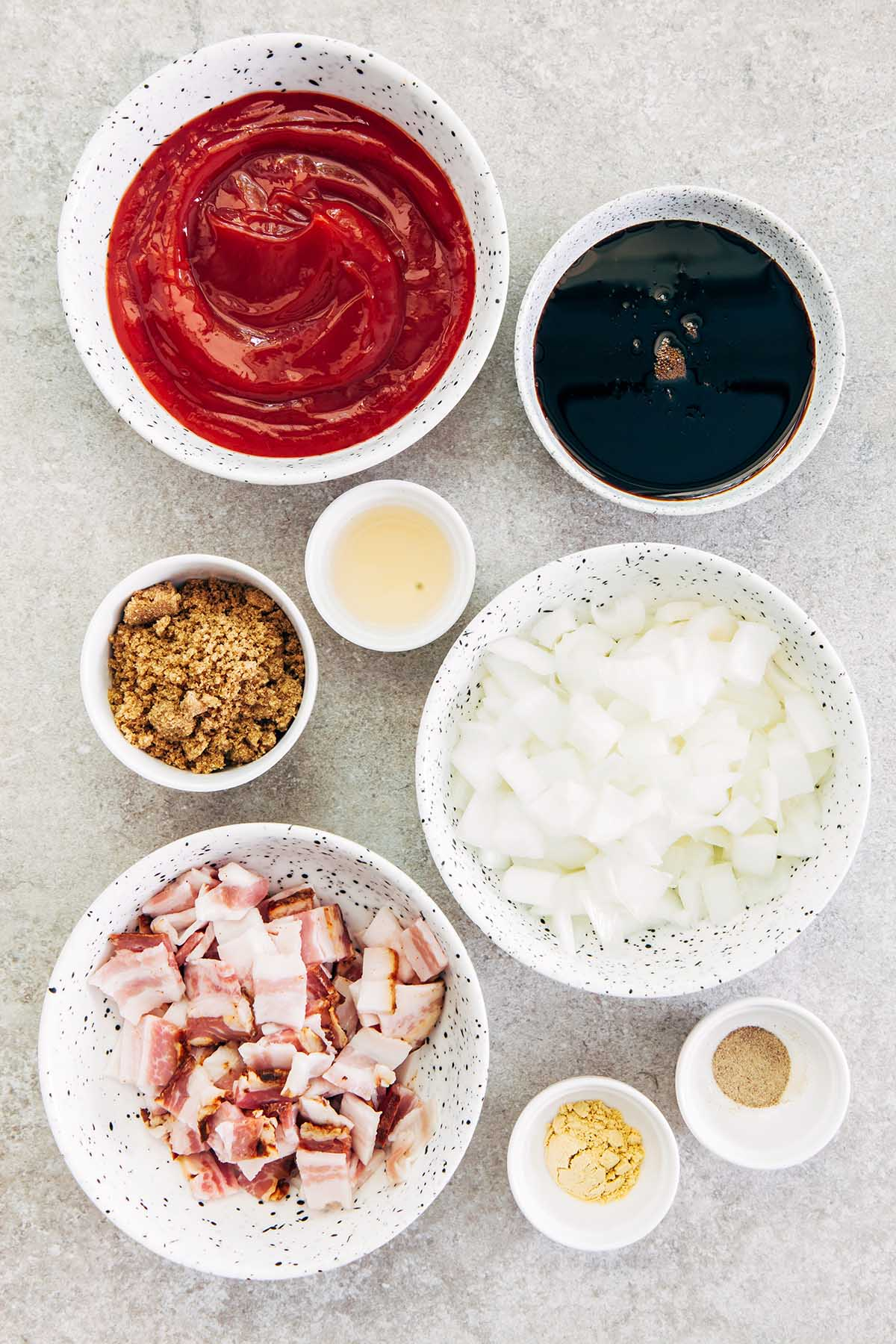 Bowls of ketchup, molasses, apple cider vinegar, brown sugar, chopped onion and bacon, ground mustard, and ground pepper on a stone surface.