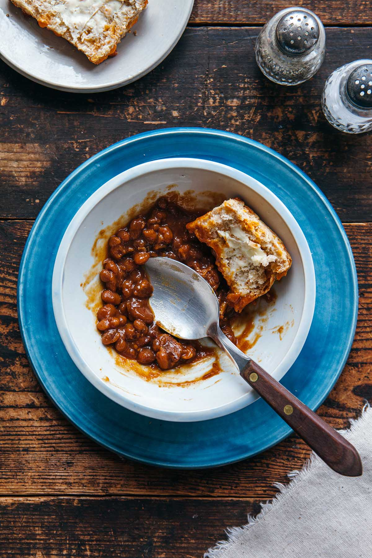 A bowl of molasses baked beans with a homemade tea biscuit.