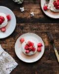 Three individual watermelon pavlovas arranged on plates on a rustic farmhouse table.