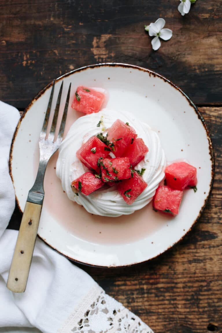 Single pavlova shell topped with watermelon on a pottery plate on a rustic table.