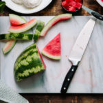 Sliced watermelon on a marble cutting board.