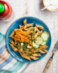Easy sesame noodles on a blue plate topped with carrot, green onion, and cucumber.