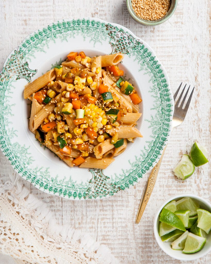 Sesame noodles with spicy corn and fresh lime in a white and green bowl.