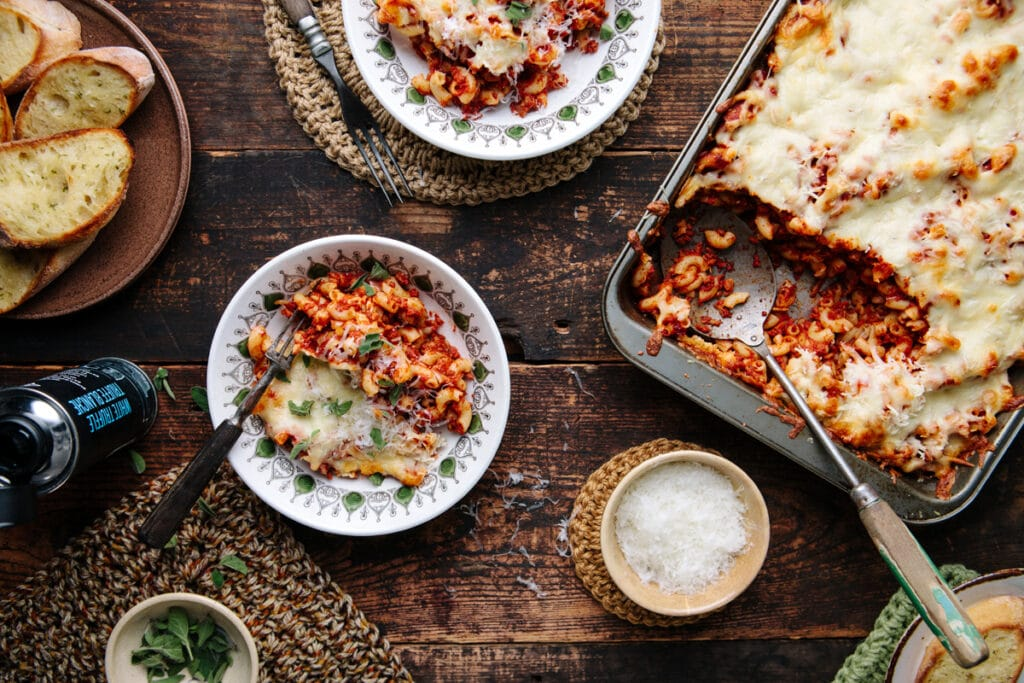 A table with a casserole dish of Easy Weeknight American-Style Goulash plus two serving bowls.