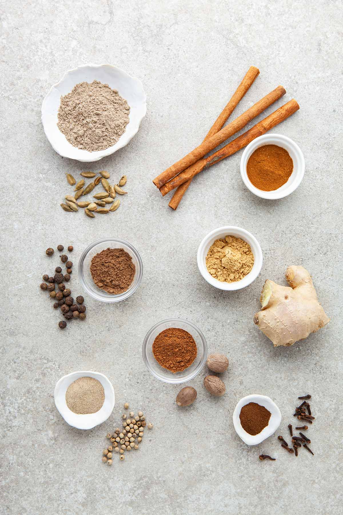 whole and ground ingredients to make homemade chai spice laid out on a stone surface.
