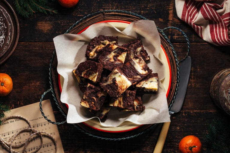 A round plate of cream cheese-swirled brownies with festive Christmas accoutrements.