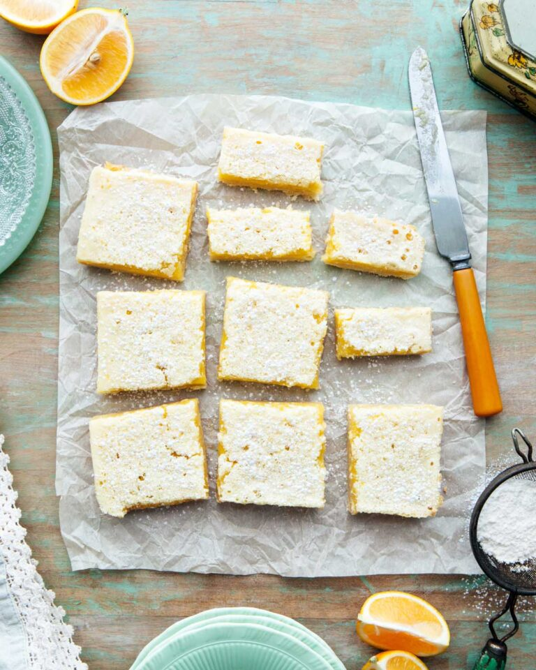 Overhead shot of classic lemon bars with shortbread crust on a green table.