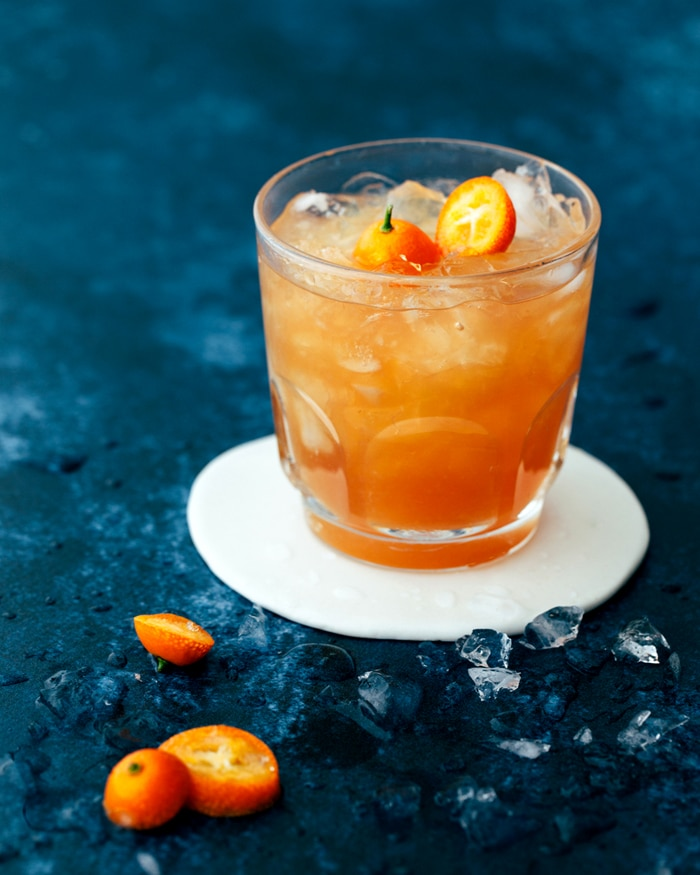 A close up of an Earl Grey Mocktail With Grapefruit And Honey in a small glass filled with crushed ice.
