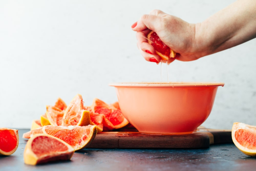 A hand over a bowl squeezing juice from a wedge of grapefruit.