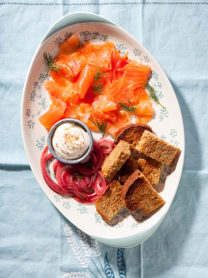 A platter of salmn gravlax, pickled red onion, toasted brown bread, and aioli with sesame seeds.
