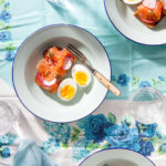 A bowl with salmon gravlax toast topped with a runny boiled egg.
